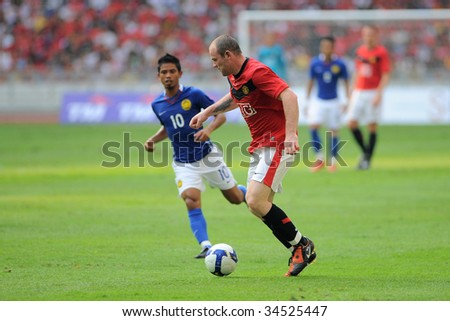KUALA LUMPUR- JULY 18: Wayne Rooney of Manchester United and Malaysian, Shafiq Rahim (no 10) in action during friendly match against Malaysia at National Stadium, July 18, 2009 in Kuala Lumpur. - stock photo