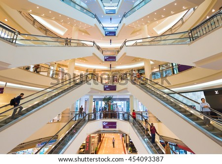 KUALA LUMPUR - JUNE 15, 2016: People move on escalators inside Suria KLCC shopping mall. The mall is located in the Kuala Lumpur City Centre district near the famous Petronas Towers. - stock photo