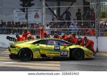 KUALA LUMPUR, MALAYSIA - AUGUST 09, 2015: Safety marshals push the Lamborghini car driven by Byron Tong to safety after it crashed in the race at the 2015 Kuala Lumpur City Grand Prix. - stock photo