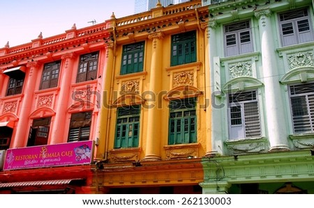 Kuala Lumpur, Malaysia - December 24, 2007: Pigeons hover on ledges above colonial-era buildings painted in bright colors in Little India - stock photo