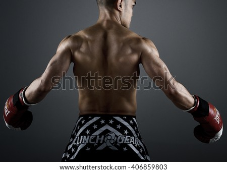 KUALA LUMPUR, MALAYSIA - DECEMBER 8TH, 2013 : Well developed MMA Fighther wearing Everlast Gloves. Shot were taken in the studio in Kuala Lumpur. Back Pose. - stock photo