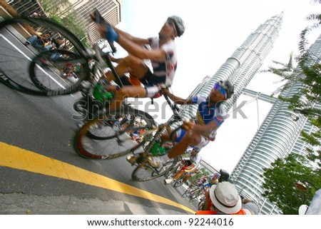 KUALA LUMPUR, MALAYSIA: FEB 15: Cyclists pedal their way in front of the iconic KLCC building landmark during the Le Tour de Langkawi competition in Kuala Lumpur,Malaysia on Feb 15,2009. - stock photo