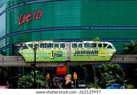 Kuala Lumpur, Malaysia - January 4, 2008:  KL Monorail car on its elevated track passing Lot 10 Shopping Center Bazaar on Bukit Bintang - stock photo