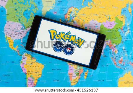 KUALA LUMPUR, MALAYSIA - 12 JULY 2016: Pokemon Go is a free-to-play, GPS based augmented reality mobile game . The game become hits around the world. (picture with world map background). - stock photo