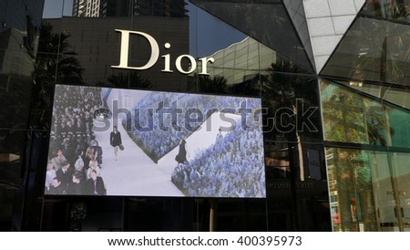 KUALA LUMPUR, MALAYSIA - March 31, 2016. Dior logo with big screen in center of Kuala Lumpur. Dior is a France luxury goods company. Headquarters in Montaigne, Paris. Founded since 1946. - stock photo