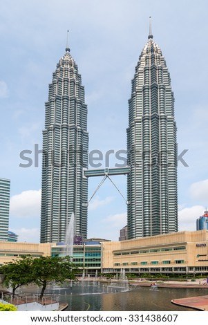 KUALA LUMPUR, MALAYSIA - 02 NOV 2014: Petronas Twin Towers, Symfoni Lake and Suria KLCC shopping mall. A famous building,beautiful architecture with a walkway between the two towers. - stock photo