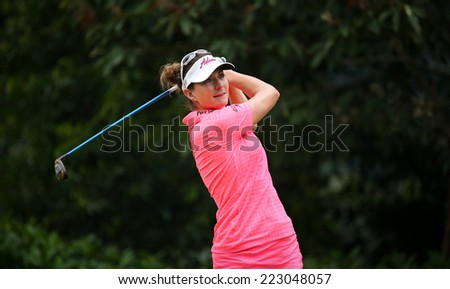 KUALA LUMPUR, MALAYSIA - OCTOBER 11, 2014: Brittany Lang of the USA tees off at the fourth hole of the KL Golf & Country Club during the 2014 Sime Darby LPGA Malaysia golf tournament. - stock photo