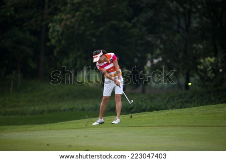 KUALA LUMPUR, MALAYSIA - OCTOBER 11, 2014: Il Hee Lee of South Korea makes a shot to the green of the ninth hole of the KL Golf & Country Club during the 2014 Sime Darby LPGA Malaysia golf tournament. - stock photo