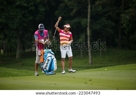 KUALA LUMPUR, MALAYSIA - OCTOBER 11, 2014: Il Hee Lee of South Korea picks her club at of the ninth hole fairway at the KL Golf & Country Club during the 2014 Sime Darby LPGA Malaysia golf tournament. - stock photo