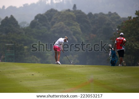 KUALA LUMPUR, MALAYSIA - OCTOBER 10, 2014: Jessica Korda of the USA plays a shot on the fairway during the 2014 Sime Darby LPGA Malaysia golf tournament in the Kuala Lumpur Golf and Country Club. - stock photo