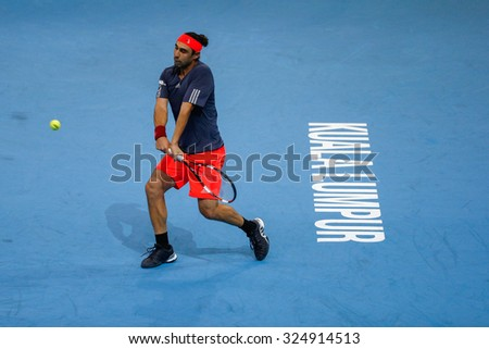 KUALA LUMPUR, MALAYSIA - OCTOBER 01, 2015: Marcos Baghdatis of Cyprus plays a backhand return during his match at the Malaysian Open 2015 Tennis tournament held at the Putra Stadium, Malaysia. - stock photo