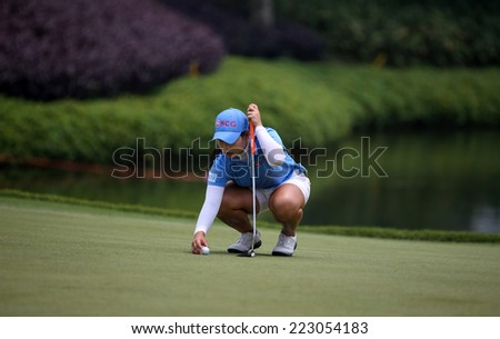 KUALA LUMPUR, MALAYSIA - OCTOBER 10, 2014: Moriya Jutanugarn of Thailand places the ball for a putt at the 18th hole of the KL Golf & Country Club at the 2014 Sime Darby LPGA Malaysia golf tournament. - stock photo