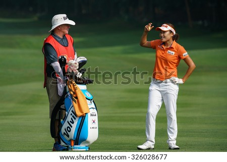 KUALA LUMPUR, MALAYSIA - OCTOBER 09, 2015: South Korea's Il Hee Lee discusses with her caddy on the 6th hole fairway of the KL Golf & Country Club at the 2015 Sime Darby LPGA Malaysia golf tournament. - stock photo