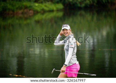KUALA LUMPUR, MALAYSIA - OCTOBER 10, 2015: USA's Jessica Korda reacts to the fans' cheers at the 18th hole of the KL Golf & Country Club during the 2015 Sime Darby LPGA Malaysia golf tournament. - stock photo