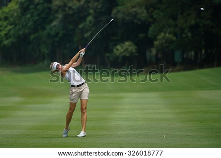 KUALA LUMPUR, MALAYSIA - OCTOBER 09, 2015: USA's Kris Tamulis plays her shot on the sixth hole fairway of the KL Golf & Country Club at the 2015 Sime Darby LPGA Malaysia golf tournament. - stock photo