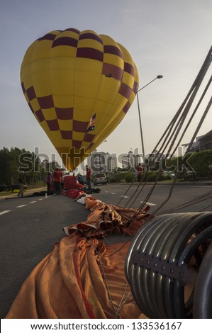 KUALA LUMPUR - MARCH 30: Balloonist of Australia, Donna Tasker has landed in the middle of the road during  5th Putrajaya International Hot Air Balloon on March 30, 2013. - stock photo