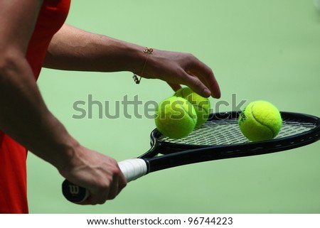 KUALA LUMPUR -MARCH 4: Jelena Jankovic chooses balls during a semi-finals match against Petra Martic at the BMW Malaysian Open on March 4,2012 in Kuala Lumpur, Malaysia. Petra Martic won [6-7(5-7),7-5,7-6 (7-5)] - stock photo