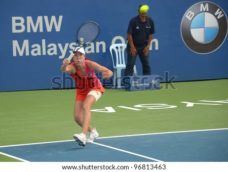 KUALA LUMPUR - MARCH 4: Jelena Jankovic returns ball during a semi-finals match against Petra Martic at the BMW Malaysian Open on March 4, 2012 in Kuala Lumpur, Malaysia. Petra Martic win [6-7(5-7),7-5,7-6 (7-5)] - stock photo