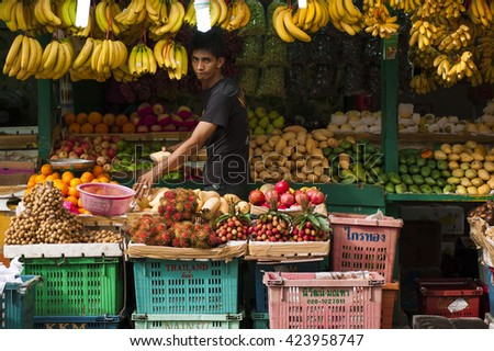 KUALA LUMPUR - MAY 21: an unidentified man selling various fruits at his stall on May 21 2016 in Chow Kit Road, KL. Fruits also included in Goods and Services Tax implemented by the government. - stock photo