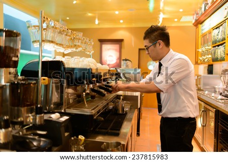 KUALA-LUMPUR - MAY 06: barman prepare coffee in airport cafe on May 06, 2014 in Kuala-Lumpur, Malaysia. Kuala Lumpur International Airport is one of the major airports of South East Asia. - stock photo