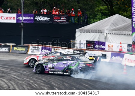 KUALA LUMPUR - MAY 19: Japan's Max Orido and Daigo Saito (back) drift in tandem at the Nations Cup competition during the Formula Drift 2012 Asia Round 1 on May 19, 2012 in Speedcity, Malaysia. - stock photo