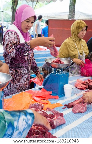 KUALA LUMPUR-OCT 15: An unidentified Malaysian Muslim prepares meat to distribute to the poor and homeless during Eid Al-Adha Al Mubarak,the Feast of Sacrifice October 15 2013 in Kuala Lumpur Malaysia - stock photo