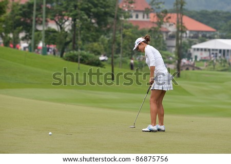 KUALA LUMPUR - OCTOBER 16: Azahara Munoz of Spain reacts after her putt on the final day of the Sime Darby LPGA Malaysia 2011 on October 16, 2011 at the Kuala Lumpur Golf & Country Club, Malaysia. - stock photo