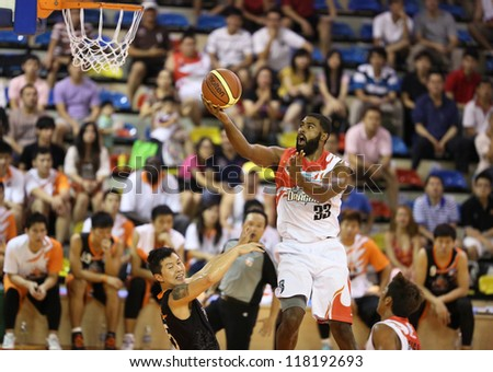 KUALA LUMPUR - OCTOBER 28: Dragons' Moala Tautaa #33 scores an easy basket against the Firehorse team in a Malaysia National Basketball League match on October 28, 2012 in Kuala Lumpur, Malaysia. - stock photo