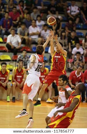 KUALA LUMPUR - OCTOBER 27: Farmcochem's Ooi Ban Sim #7 shots over Dragons'   Kuek Tian Yuan #10 in a Malaysia National Basketball League match October 27, 2012 in Kuala Lumpur, Malaysia. - stock photo