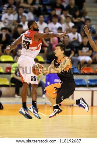 KUALA LUMPUR - OCTOBER 28: Firehorse's Lau Bik Ing (black) sails past Dragon's Moala Tautaa #33 to score in a Malaysia National Basketball League match on October 28, 2012 in Kuala Lumpur, Malaysia. - stock photo