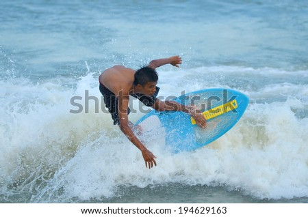 KUANTAN - DECEMBER 29: unidentified surfer in action catching waves in evening at Teluk Cempedak beach on December 29, 2012 in Kuantan, Pahang, Malaysia. - stock photo