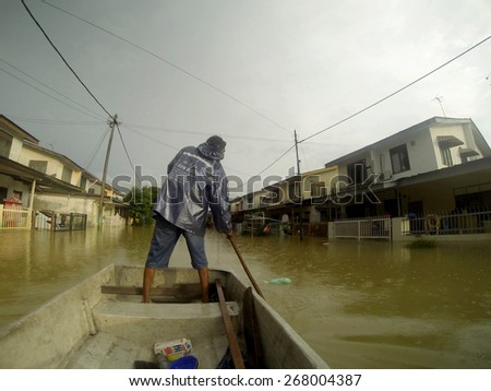 KUANTAN, PAHANG MALAYSIA-DEC 05, 2014:Unidentified boy is rowing a boat to enter his home after struck by the worst floods in history - stock photo