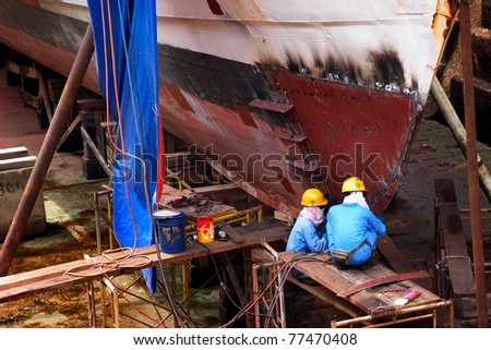 KUCHING, BORNEO ISLAND - MAY 13: Shipyard workers repair a ship in the dry dock beside the Sarawak River, May 13, 2011 in Kuching, Borneo Island. Boats and ships are important forms of transport here. - stock photo