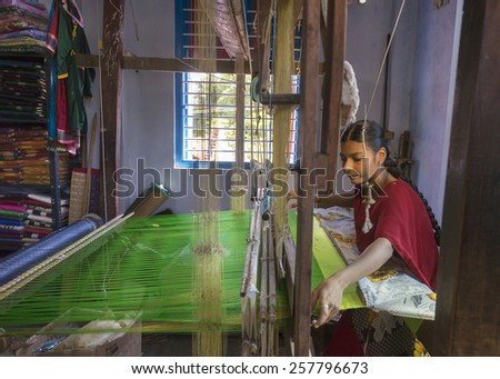 KUMBAKONAM, INDIA - OCTOBER 11, 2013: Home silk sari weaving on a hand loom set in a small room. The young woman works on a green piece of textile. - stock photo