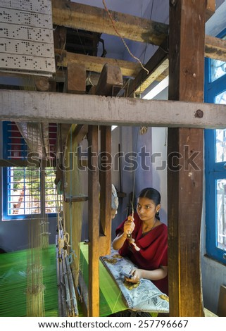 KUMBAKONAM, INDIA - OCTOBER 11, 2013: Home silk sari weaving on a hand loom set in a small room of the modest home. The young woman works on a green piece of textile. - stock photo