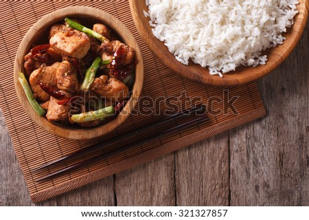 Kung pao chicken fillets in a bowl close up and rice. horizontal view from above - stock photo