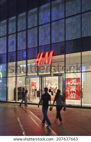 KUNMING-JULY 6, 2014. H&M outlet at night. Hennes & Mauritz is active in 48 markets with a total of 2,776 stores. The company opened its first store in China in 2007, currently it has 134 stores. - stock photo
