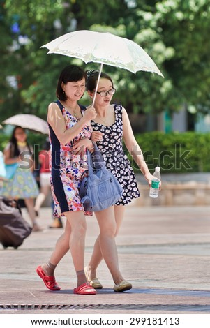 KUNMING-JULY 10, 2014. Mother and daughter with umbrella as sun blocker. Since ancient times a pale skin is an absolute Chinese beauty ideal. A tanned skin is often associated with low class workers. - stock photo
