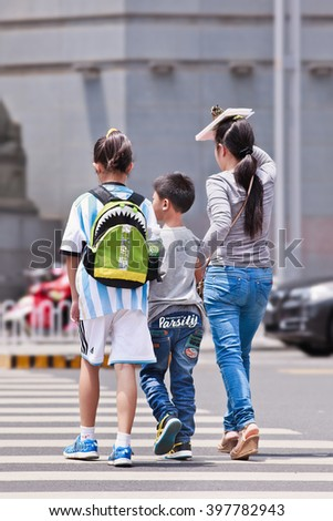 KUNMING-JULY 5, 2014. Woman with children on zebra crossing. Xinhua reported on 29 Oct. 2015 the new policy allowing Chinese couples to have two children in order to help address China's aging issue. - stock photo