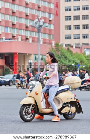 KUNMING-JUNE 30, 2014. Girl on an e-bike. An estimated 200 million Chinese now use e-bikes, 1,000-fold increase from 15 years ago. About 90 percent of world's e-bikes were sold in China in 2012. - stock photo