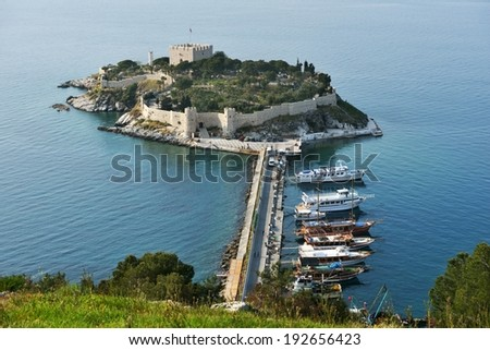 KUSADASI, TURKEY - APRIL 7, 2014: View to the castle on Pigeon island. Built in Byzantine Era, now the castle houses the museum and is the lovely place for many tourists - stock photo