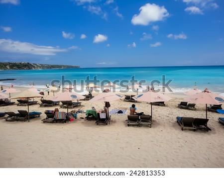 KUTA, INDONESIA - AUGUST 20, 2013: Unidentified tourists at Dreamland beach at Bali. Dreamland Beach is a beautiful panoramic coral beach appointed as best surfing point in Bali. - stock photo