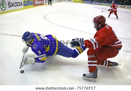 KYIV, UKRAINE - APRIL 20: Dmytro Nimenko of Ukraine (L) fights for a puck with Michal Kotlorz of Poland during their IIHF Ice-hockey World Championship DIV I game on April 20, 2011 in Kyiv, Ukraine - stock photo