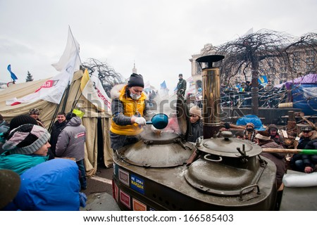 KYIV, UKRAINE - DEC 8: Woman prepares a tea on a huge street kitchen on the crowded Maidan square during two weeks anti-government protest on December 8, 2013, in Kiev, Ukraine. - stock photo