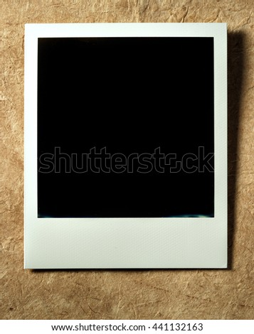 KYIV, UKRAINE - FEB 12, 2014: Polaroid photo cards on craft paper background. - stock photo