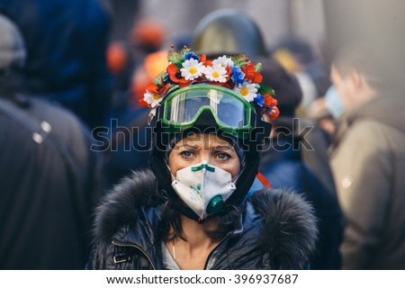 Kyiv, Ukraine - February 18, 2014: Ukrainian woman protester with wreath. During violent confrontation on Instytutska Street when police trying to oust protesters from the government quarter.  - stock photo
