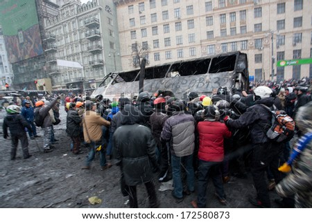 KYIV, UKRAINE - JAN 21: Angry crowd on the occupying street overturned burned-out bus on the demostration during anti-government protest Euromaidan on January 21, 2014, in center of Kiev, Ukraine.  - stock photo