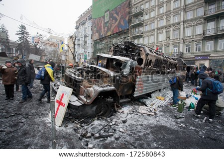 KYIV, UKRAINE - JAN 21: People walk around the barricades with burned out military cars on the snow street during anti-government protest on January 21, 2014, in Kiev, Ukraine.   - stock photo
