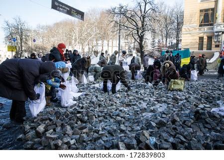 KYIV, UKRAINE - JAN 23: Peoples picking stones on Hrushevskogo street during anti-government protest Euromaidan on January 23, 2014, in center of Kiev, Ukraine - stock photo