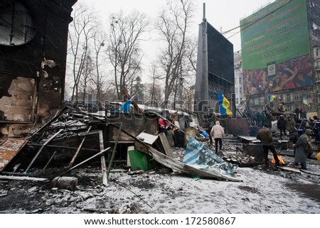 KYIV, UKRAINE - JAN 21: Police Force stand behind burned barricades built by crowd of people on the occupying street during anti-government protest Euromaidan on January 21, 2014, in Kiev, Ukraine.  - stock photo